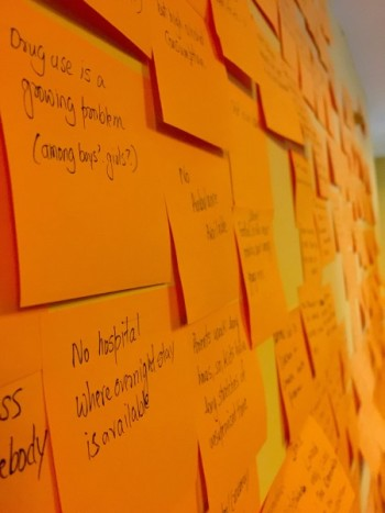 Observations and insights from the interviews written on sticky notes and pasted on a wall for the team to start ideation on